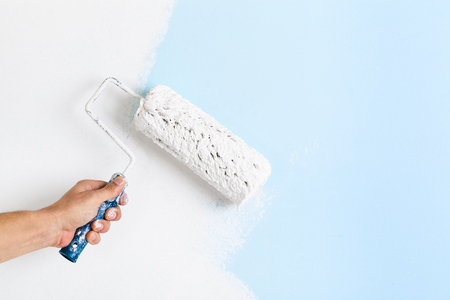 Close up of painter arm painting a wall with paint roller; copy space Stock Photo