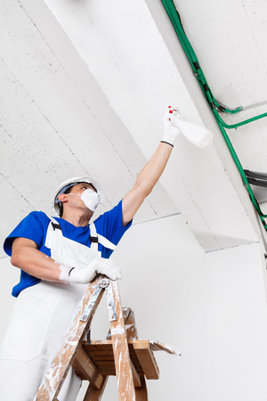 mildewed: worker with helmet, gloves and mask spraying ceiling with spray bottle on wooden vintage ladder, bottom view