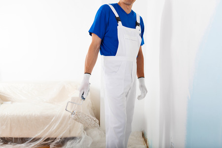 dungarees: headless portrait of painter in white dungarees and gloves with paint roller, side view