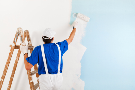 Back view of  painter with cap and gloves painting a wall with paint roller and wooden vintage ladder, with copy space Banque d'images