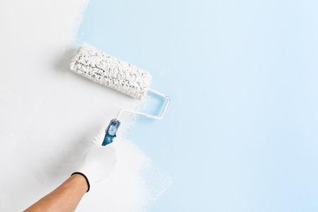Zamknąć malarza ręką w białej rękawiczce malując ścianę z wałkiem; kopia przestrzeń