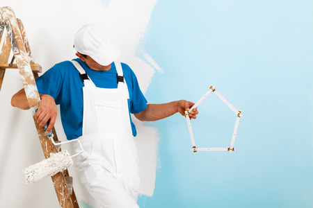 yardstick: portrait of painter man with paint roller and wooden vintage ladder showing a yardstick shaped as an house, with copy space Stock Photo
