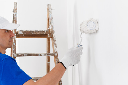 painting decorating: side view of  painter in white dungarees, cap and gloves painting a wall with paint roller and wooden vintage ladder, with copy space
