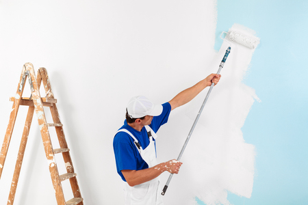 painter with cap painting a wall with paint roller and wooden vintage ladder, with copy space