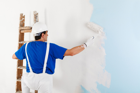 dungarees: Back view of  painter in white dungarees, helmet and gloves painting a wall with paint roller and wooden vintage ladder, with copy space