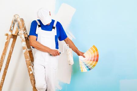 paintroller: portrait of painter man with paintroller and vintage wooden leddar showing a color palette