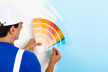 achteraanzicht van schilder man zoekt een kleurenpalet op de helft geschilderde muur, met een kopie ruimte