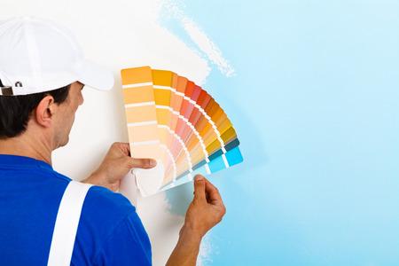 Vista posteriore del pittore uomo alla ricerca di una tavolozza di colori sulla parete dipinta a metà, con lo spazio della copia Archivio Fotografico - 52884334