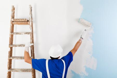 HOMBRE PINTANDO: Vista posterior del pintor en un peto blanco, casco y guantes de pintar una pared con rodillos de pintura y escalera de madera de época, con espacio de copia Foto de archivo