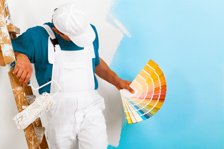 portrait of painter man with paintroller and wooden vintage ladder showing a color palette, on half painted wall