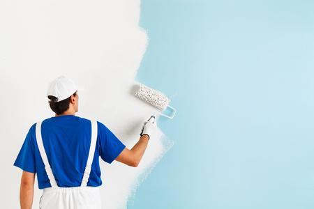 Rückansicht des Malers in der weißen Latzhose, blaues T-Shirt, Mütze und Handschuhe, die eine Wand mit Farbroller, mit Kopie Raum Malerei