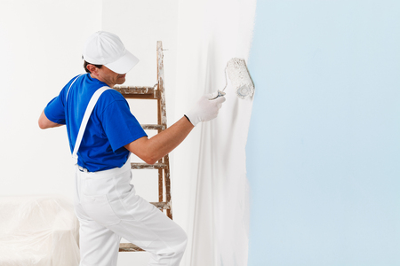 dungarees: side view of  painter in white dungarees, cap and gloves painting a wall with paint roller and wooden vintage ladder, with copy space