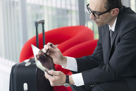telephone salesman: Business man with trolley using his Tablet on red armchair at exhibition lobby