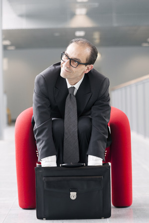 man searching: Business man searching for something in briefcase sitting on a red armchair