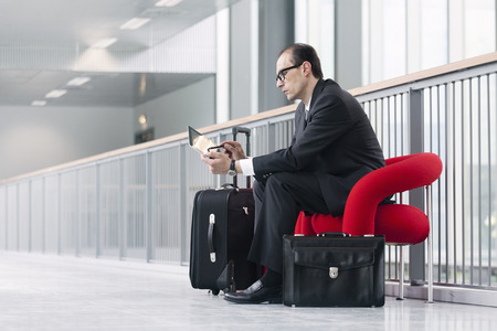 business lounge: Business man with trolley using his Tablet on red armchair at exhibition lobby