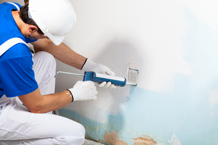 Close-up Of Professional Workman Applying Silicone Sealant With Caulking Gun on the Wall Banque d'images