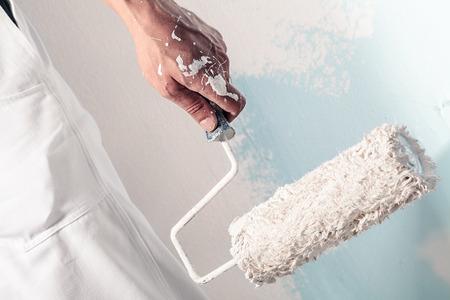 Sluit omhoog van Professionele Workman Hand die Vuile Paintroller houden Stockfoto