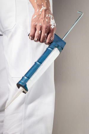 sealant: Close up Of Professional Workman Hand holding Caulking Gun for Silicone Sealant Stock Photo