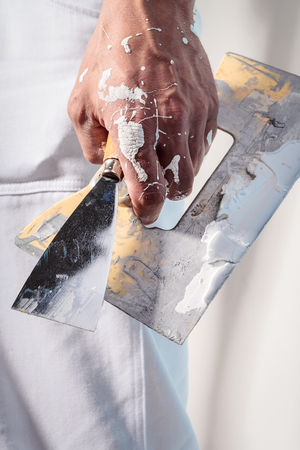 Close up Of Professional Workman Hand holding Putty Knife with Plaster