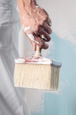 whitewash: Close up Of Professional Workman Hand holding Dirty Paintbrush