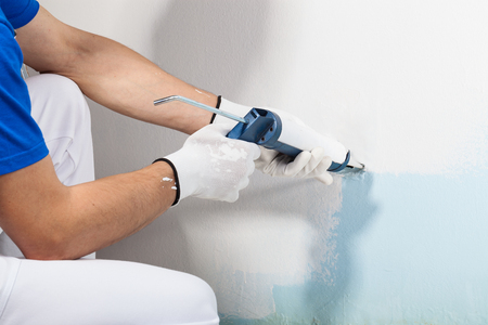 sealant: Close-up Of Professional Workman Applying Silicone Sealant With Caulking Gun on the Wall Stock Photo