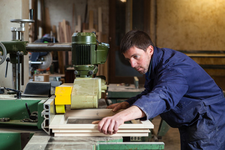 buzz saw: Portrait of Carpenter man cutting wooden window with tablesaw in workshop Stock Photo
