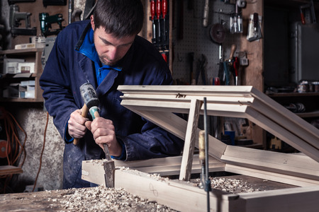wood furniture: Portrait of Carpenter using Hammer and Chisel on a Wooden Window in his Workshop