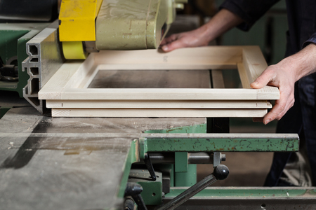 buzz saw: Close up of Carpenters hands cutting wooden window frame with tablesaw in workshop
