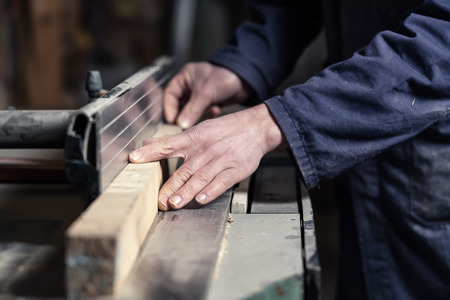 buzz saw: Close up of Carpenters hands cutting wood with tablesaw in workshop; selective focus Stock Photo