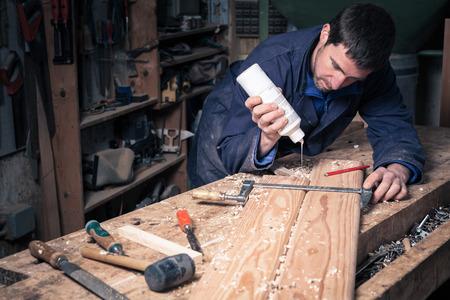 resistol: Retrato de carpintero poniendo pegamento en tablas de madera en su taller; enfoque selectivo Foto de archivo