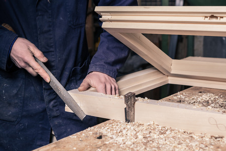 Close-up of a Carpenter working on a Wooden Window Frame with a File in his Workshop; Selective Focus
