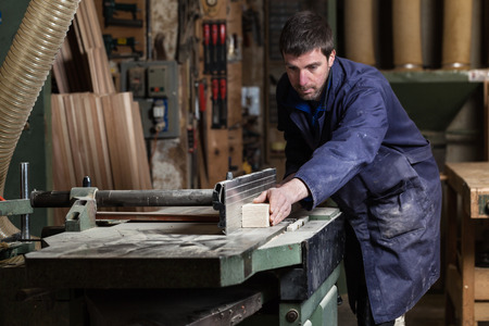 buzz saw: Portrait of Carpenter man cutting wood with tablesaw in workshop
