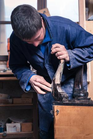 muebles de madera: Retrato de carpintero restauración de muebles de madera con papel de lija en su taller. Foto de archivo
