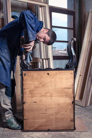 wood furniture: Portrait of Carpenter restoring Wooden Furniture with sandpaper in his workshop.
