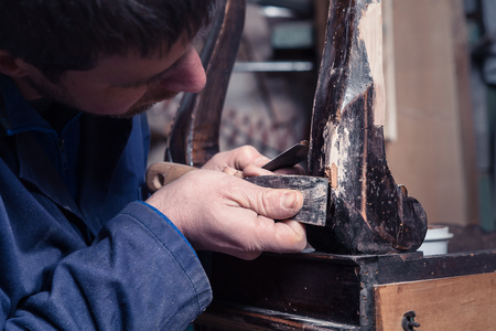 restoring: Portrait of Carpenter restoring Wooden Furniture with plaster and putty Knife in his workshop.