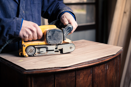 finishing: Close up of Carpenter restoring old wooden furniture with belt sander in his Wood Shop Stock Photo