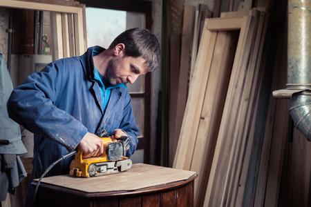 wood furniture: Portrait of Carpenter restoring old wooden furniture with belt sander in his Wood Shop