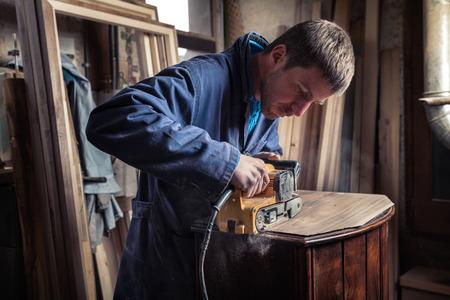 old furniture: Portrait of Carpenter restoring old wooden furniture with belt sander in his Wood Shop