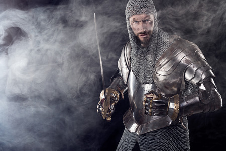 templar: Portrait of Medieval Dirty Face Warrior with chain mail armour and red cross on sword. Cloud smoke on Dark Background Stock Photo