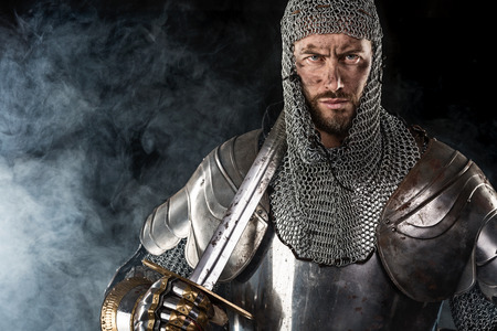 Portrait of Medieval Dirty Face Warrior with chain mail armour and red cross on sword. Cloud smoke on Dark Background Standard-Bild