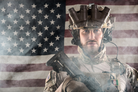 night vision: Portrait of Bearded US Army Soldier With Night Vision Goggles on American Flag Background; Smoke Cloud