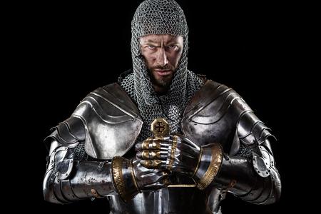 Porträt des mittelalterlichen schmutzigen Gesicht Krieger mit Kettenrüstung und rotes Kreuz auf Schwert. Schwarzer Hintergrund