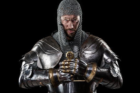 Portrait of Medieval Dirty Face Warrior with chain mail armour and red cross on sword. Black Background