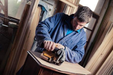 carpenter's sawdust: Portrait of Carpenter restoring old wooden furniture with belt sander in his Wood Shop