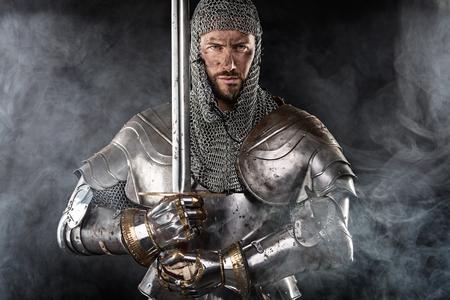 Porträt des mittelalterlichen schmutzigen Gesicht Krieger mit Kettenrüstung und rotes Kreuz auf Schwert. Wolke Rauch auf dunklem Hintergrund Standard-Bild