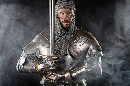 chain armour: Portrait of Medieval Dirty Face Warrior with chain mail armour and red cross on sword. Cloud smoke on Dark Background Stock Photo