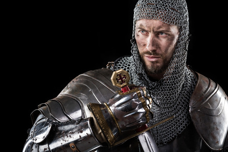 Portrait of Medieval Dirty Face Warrior with chain mail armour and red cross on sword. Dark Background