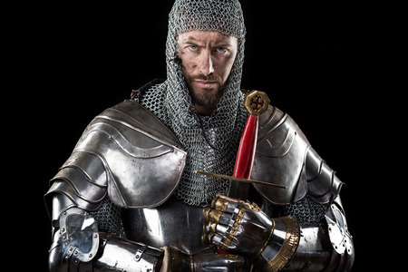 chivalry: Portrait of Medieval Dirty Face Warrior with chain mail armour and red cross on sword. Dark Background