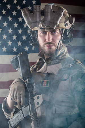 us soldier: Portrait of Bearded US Army Soldier With Night Vision Goggles on American Flag Background; Smoke Cloud