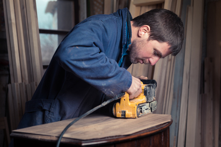 sander: Portrait of Carpenter restoring old wooden furniture with belt sander in his Wood Shop